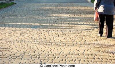 Walking grandma in the park. Cobblestones surface.