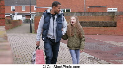 Walking Home from the Shops - Man and his daughter are...