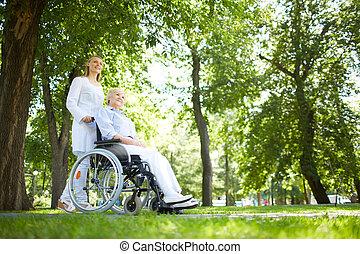 Walking in park - Pretty nurse walking with senior patient...