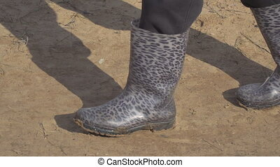 Walking in rubber boots on the sand - Man walking in rubber...