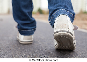 Walking in sport shoes on pavement - Teenager walking in ...