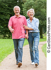 Walking in the park - Active and happy senior couple walking...