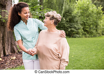 Walking in the park - Elder woman and caregiver walking in...