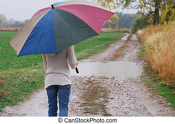 Young woman walking on a country dirt road with an umbrella in the rain.