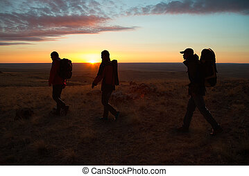Walking in the sunglow hikers - The three hikers walk trip,...