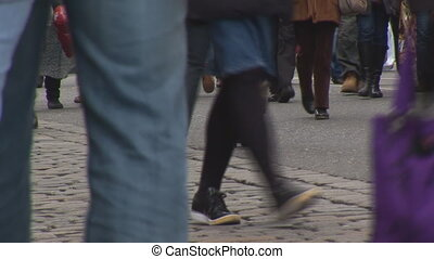 walking legs of busy people on shopping street, close