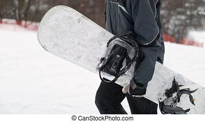Walking Man Holding Snowboard - Close Up of Walking Man Hand...