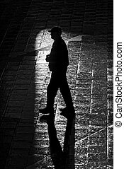 Walking man with long shadows in high contrast