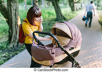 walking Mother with baby carriage
