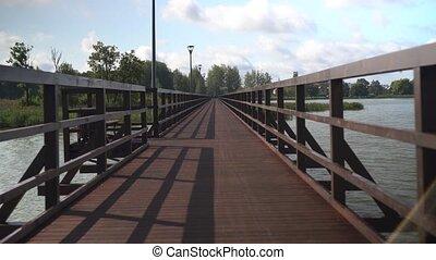 Walking On A Wooden Bridge Footbridge. Camera movement forward shot with gimbal.