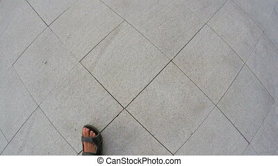 Walking on pavement slab - In open shoes man walking on...