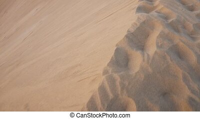 Walking on the edge of a sand dune in desertic landscape. -...
