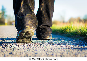 walking on the road - man walking on the road alone in the...