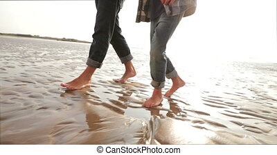 Walking on the Wet Sand - Low angle, tracking shot, of a...