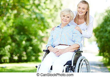 Walking out with patient - Female caregiver and senior ...