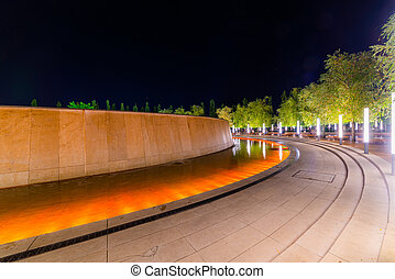 Walking path around fountain in resort with colored light illumination and trees on side at evening. Modern park design