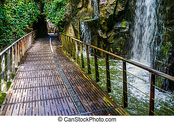 Walking path with a waterfall, beautiful nature and garden architecture