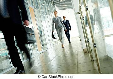 Walking people - Businesspeople going along corridor inside...