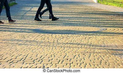 Walking people on the cobbles. Cobblestones surface in the park.