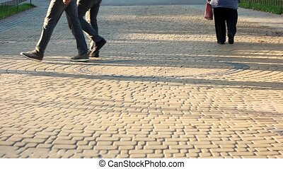 Walking people on the cubblestone pavement.