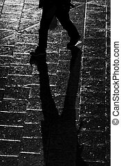 Walking person with long shadows in high contrast