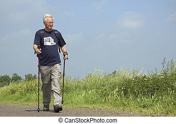 Walking Senior - Senior man doing a Nordic Walk on a sunny...