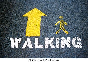 Walking symbol. - Walking symbol displayed outdoors.