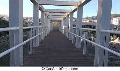 walking through bridge to elevator