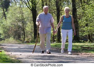 Walking through the park - Elderly couple walking through...