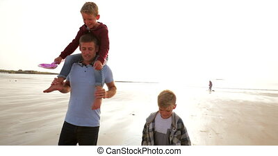 Walking up from the Waters Edge at the Beach - Father and...