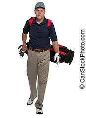 Walking up the fairway - Male golfer walking along carrying...