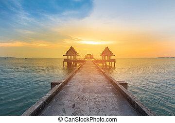 Walking way leading to sunset ocean skyline