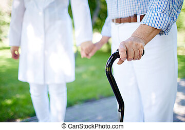 Walking with cane - Close-up of disabled female hand holding...