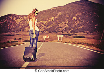 walking with suitcase - Attractive young woman hitchhiking ...