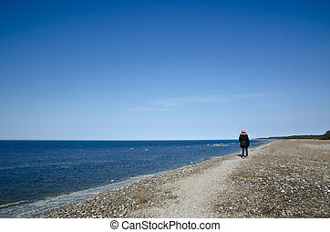 Walking woman along coast