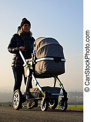 Walking woman with baby stroller in sunny day.