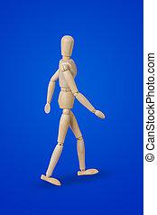 Walking wooden toy figure on blue