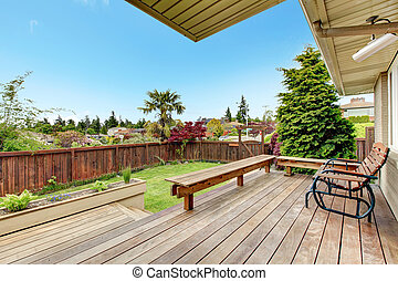 Wooden deck with benches and chair. View of fenced backyard with lawn and flower bed