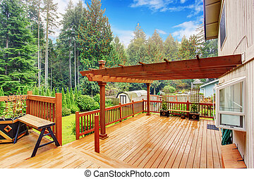 Spacious wooden deck with benches and attached pergola