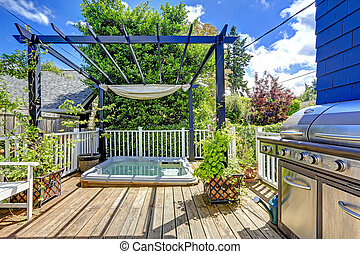 Walkout deck with jacuzzi and pergola. Patio area with barbecue