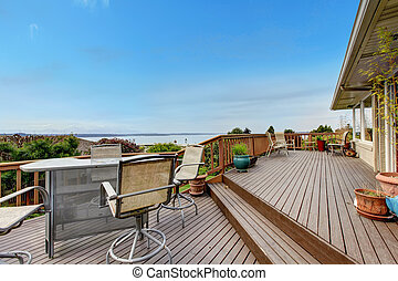 Walkout deck with patio area and water view
