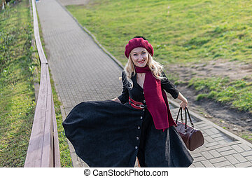 walks up the stairs and in a burgundy palette and biret, with a beautiful smile in black clothes, in the fall against the blue sky.