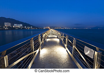 Walkway bridge along the coast at night