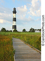 Walkway leading to the Bodie Island lighthouse over marshes of the Cape Hatteras National Seashore against white clouds and a blue morning sky vertical
