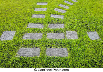 Walkway sheet stretching into the distance with green grass lawn in perspective view in garden. Garden landscape design concept, A row of square-shaped walkways in the public park.