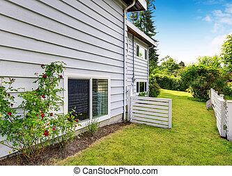 Walkway to backyard area of siding American house.