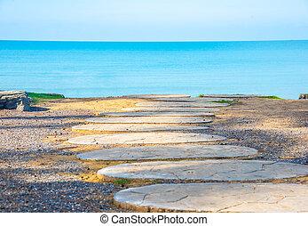 walkway to beach with blue sky .