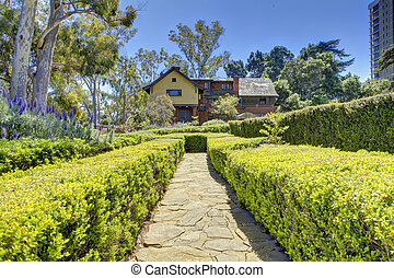 Picturesque walkway with trimmed hedges to Marston House Museum & Gardens. San Diego, CA