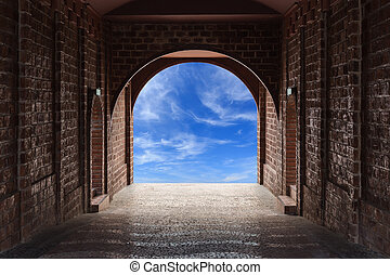 Walkway tunnel made by red brick and view of blue sky with...