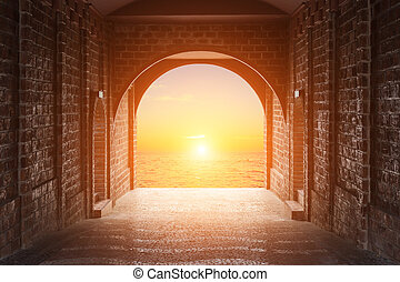 Walkway tunnel made by red brick and view of sunset or...